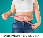 fat woman measuring her stomach | Shutterstock . vector #1194379414