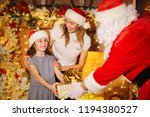 santa claus gives a gift to a... | Shutterstock . vector #1194380527