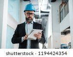 middle aged engineer in hardhat | Shutterstock . vector #1194424354