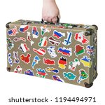 suitcase in hand with stickers... | Shutterstock . vector #1194494971