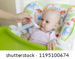 a small one year old child eats ... | Shutterstock . vector #1195100674