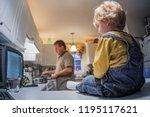 toddler boy sitting on kitchen... | Shutterstock . vector #1195117621