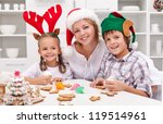 Happy family with seasonal hats decorating christmas gingerbread cookies - stock photo