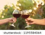 couple with glasses of red wine ... | Shutterstock . vector #1195584064