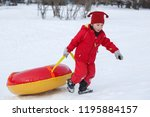 a child in a red jumpsuit rolls ... | Shutterstock . vector #1195884157