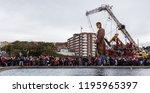 crowds watch the giant man walk ...   Shutterstock . vector #1195965397