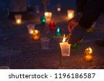a man lights a candle standing... | Shutterstock . vector #1196186587