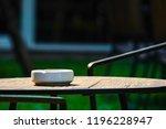 white ashtray on the dark wood...   Shutterstock . vector #1196228947