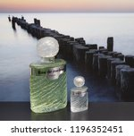 Small photo of Eau de Rochas fragrance for ladies big perfume bottle next to a commercial perfume bottle in front of the picture of a groyne in the sea Kassel Germany 09 15, 2018 Rochas is a French perfume provider