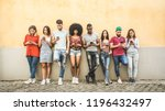 Stock photo multiracial friends using smartphone against wall at university college backyard young people 1196432497