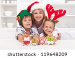 Happy woman and kids in christmas hats making gingerbread cookie family - stock photo