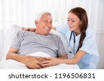 nurse looking at happy male... | Shutterstock . vector #1196506831