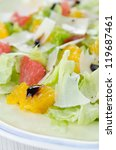Selective focus on the grated cheese and slices of orange on a plate with salad closeup - stock photo