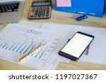 gold pen on charts with phone... | Shutterstock . vector #1197027367