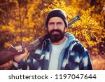 bearded hunter man holding gun... | Shutterstock . vector #1197047644
