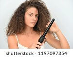 satisfied curly hair girl holds ... | Shutterstock . vector #1197097354