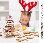 Christmas kids dressed as reindeer  decorating gingerbread cookies - focus on foreground - stock photo