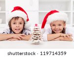 Happy kids at christmas time with a gingerbread tree they decorated - stock photo