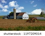 Small photo of Old Amish White Wooden Barn and Farm Equipment on a Sunny Summer Day