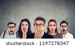 Small photo of Shocked man in glasses and his scared friends pose against gray wall background. Emotional horrified group people see something unexpected. Human reaction concept