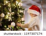 little boy wearing santa hat...   Shutterstock . vector #1197307174