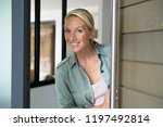 blond woman welcoming people at ... | Shutterstock . vector #1197492814
