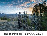Three adult male hunter friends, unrecognizable,  stand on a mountain ridge looking for elk to hunt during bow archery season. Wearing camouflage - stock photo