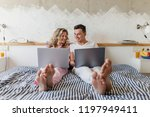 young couple sitting on bed in... | Shutterstock . vector #1197949411