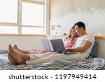 young couple sitting on bed in... | Shutterstock . vector #1197949414