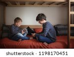 brothers play gadgets on two... | Shutterstock . vector #1198170451
