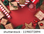 Christmas background with gift boxes, clews of rope, paper's rools and decorations on red. Preparation for holidays. Top view with copy space. - stock photo