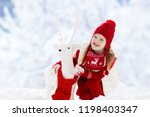 child playing with reindeer in... | Shutterstock . vector #1198403347
