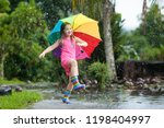Small photo of Kid playing out in the rain. Children with umbrella and rain boots play outdoors in heavy rain. Little girl jumping in muddy puddle. Kids fun by rainy autumn weather. Child running in tropical storm.