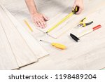 man installing timber laminate... | Shutterstock . vector #1198489204