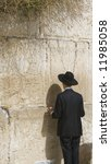 this is a Hasidic Man Praying at the Western Wall, Jerusalem during Passover Week. - stock photo