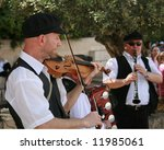 This is Three musicians outside the Western Wall Jerusalem during Passover Week. - stock photo