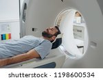 Stock photo patient lying on the tc scanner bed waiting to be scanned 1198600534