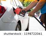 man pumping gasoline fuel in... | Shutterstock . vector #1198722061