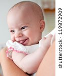 Mother holding a cute smiling baby girl - stock photo