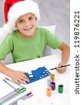 Boy making christmas greeting card wearing santa hat - stock photo