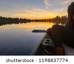 a woman canoeing at sunset at...