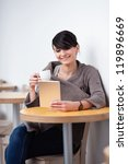 Young happy woman sitting in the restaurant with digital tablet, drinking coffee - stock photo