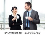Businessman and businesswoman drinking coffee - stock photo