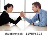 Businessman and businesswoman arm wrestling on desk in office - stock photo