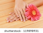 Woman hands with french manicure and flower on wooden background - stock photo