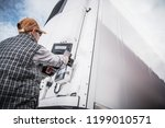 Refrigerated Semitrailer Cargo. Adjusting Temperature by Caucasian Truck Driver. - stock photo