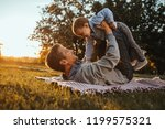 daddy and son are playing in a... | Shutterstock . vector #1199575321
