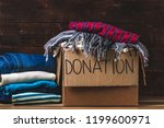 Small photo of Donation concept. Donation box with donation clothes on a wooden background. Charity. Help for people in need