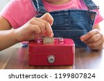 Small photo of accumulate for poor people or investment .coins,hand and red moneybox on the white background for charity foundation concept.child throwing money into piggy bank.