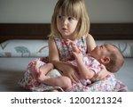 little sister hugging her... | Shutterstock . vector #1200121324